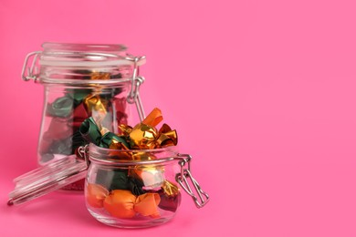 Candies in colorful wrappers on pink background. Space for text
