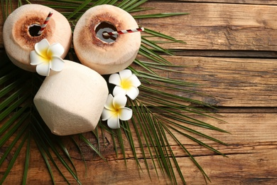 Fresh coconuts with drinking straws and flowers on wooden table, flat lay. Space for text