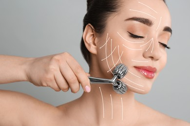 Woman using metal face roller on grey background, closeup