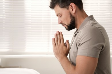 Religious man praying indoors. Space for text