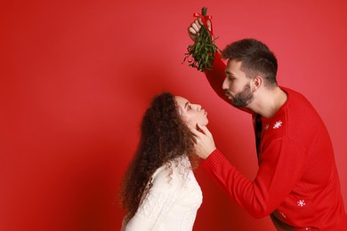 Lovely couple under mistletoe bunch on red background. Space for text