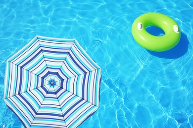 Open beach umbrella and inflatable ring floating in swimming pool