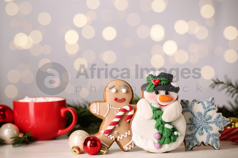 Sweet Christmas cookies and decor on white table against blurred festive lights