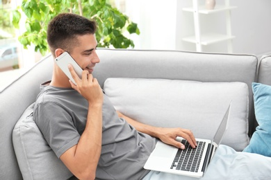 Man talking by mobile phone while using laptop on sofa at home