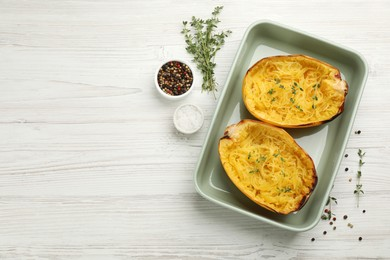Halves of cooked spaghetti squash in baking dish, thyme and spices on white wooden table, flat lay. Space for text
