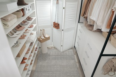 Dressing room interior with clothes rack and collection of stylish shoes, above view