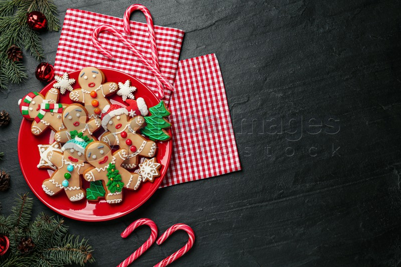 Flat lay composition with delicious Christmas cookies on black table, space for text