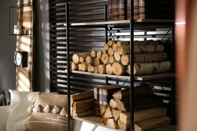 Shelving unit with stacked firewood and books near wall in room. Idea for interior design