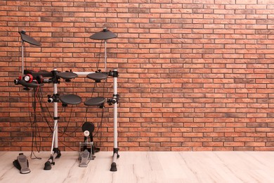 Modern electronic drum kit near red brick wall indoors, space for text. Musical instrument