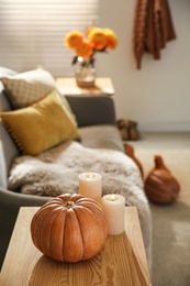 Pumpkin and burning candles on wooden table in room. Cozy interior inspired by autumn colors