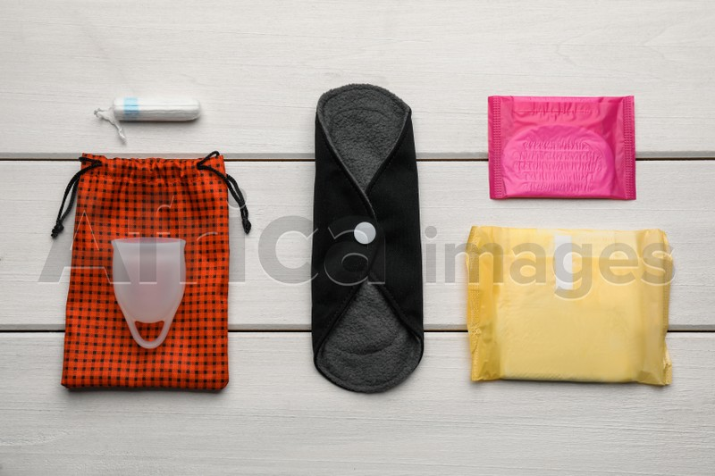 Cloth menstrual pad near other reusable and disposable female hygiene products on white wooden table, flat lay