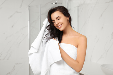 Young woman drying hair with towel in bathroom
