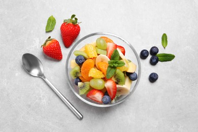 Delicious fresh fruit salad in bowl on light table, flat lay