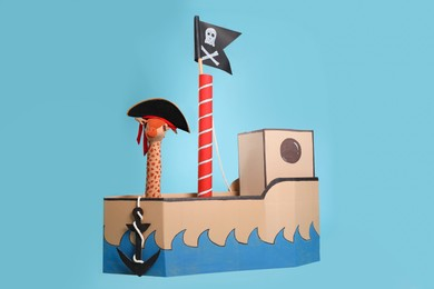 Pirate cardboard ship with flag on turquoise background