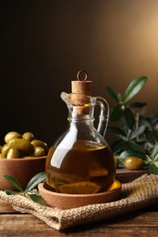 Glass jug of oil, ripe olives and green leaves on wooden table