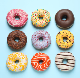 Delicious glazed donuts on light blue background, flat lay