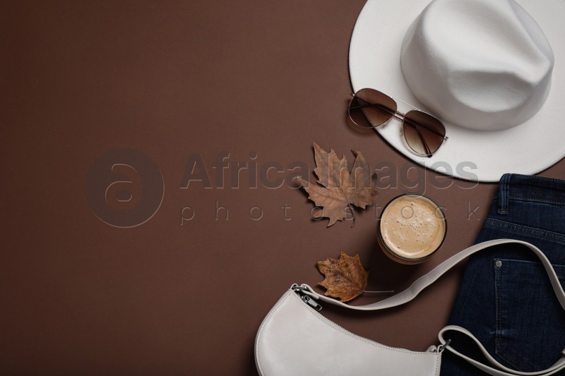 Flat lay composition with stylish hat and coffee on brown background, space for text