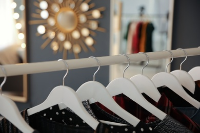 Collection of modern clothes hanging on rack indoors