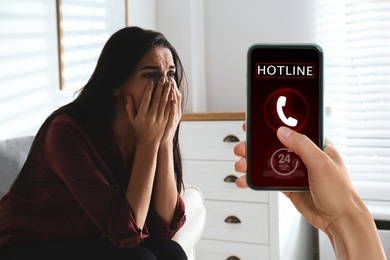 Calling domestic violence hotline. Abused young woman crying indoors