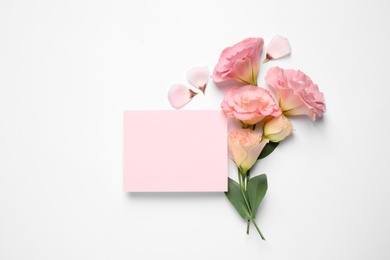 Beautiful Eustoma flowers and blank card on white background, flat lay. Space for text