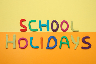 Phrase School Holidays made of modeling clay on color background, top view