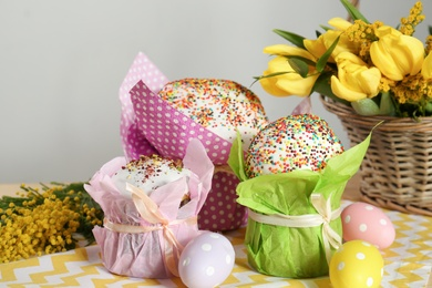 Delicious Easter cakes, dyed eggs and basket with flowers on table