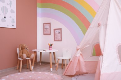 Cute child's room interior with stylish furniture, toy tent and rainbow art on wall