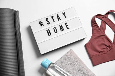 Stylish sportswear, yoga mat and light box with hashtag Stay at Home on white background, flat lay. Self isolation during COVID‑19 pandemic