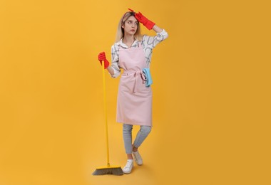 Young housewife with broom on yellow background