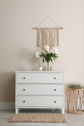 Room interior with white chest of drawers near beige wall