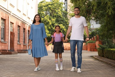 Parents taking their daughter to school in morning