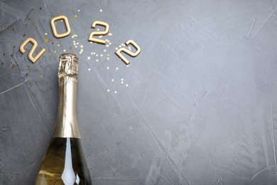Bottle of sparkling wine, gold confetti and number 2022 on grey background, flat lay with space for text. Happy New Year