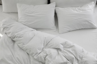 Many soft pillows and blanket on large comfortable bed