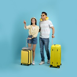 Couple of tourists with suitcases on light blue background