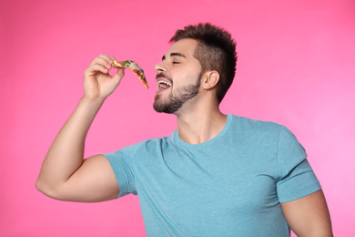 Handsome man eating pizza on pink background