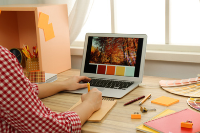 Female designer working at wooden table indoors, closeup