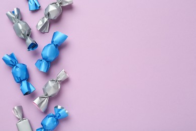 Many candies in light blue and silver wrappers on violet background, flat lay. Space for text