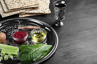 Passover Seder plate (keara) with traditional meal on black table, space for text. Pesah celebration