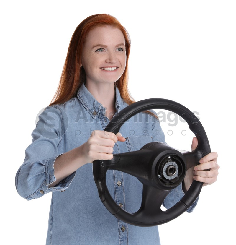 Happy young woman with steering wheel on white background