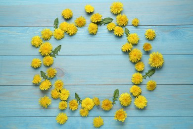 Frame of beautiful yellow dandelions on light blue wooden table, flat lay. Space for text