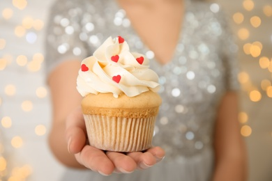 Woman holding tasty cupcake for Valentine's Day against blurred lights, closeup