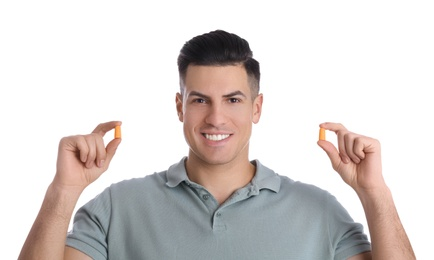 Man with foam ear plugs on white background