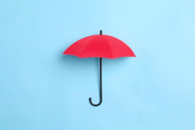 Bright toy umbrella on light blue background, top view