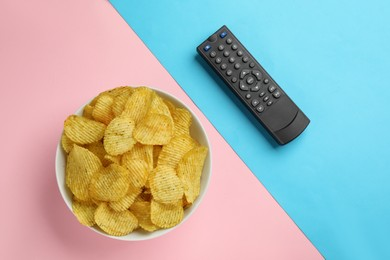 Modern tv remote control and chips on color background, flat lay