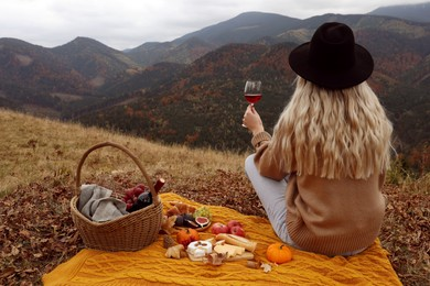 Young woman with glass of wine having picnic in mountains on autumn day, back view. Space for text