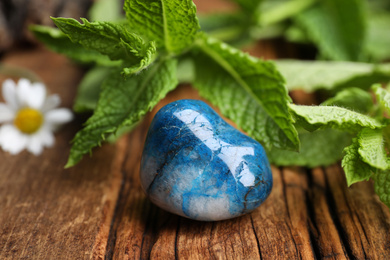 Beautiful blue shattuckite stone and fresh healing herbs on wooden table