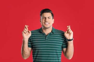 Man with crossed fingers on red background. Superstition concept