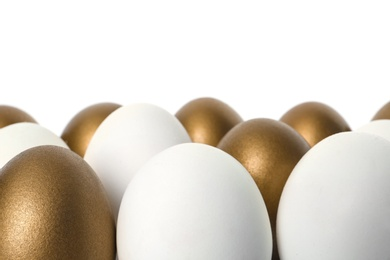 Golden eggs among others on white background