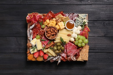 Assorted appetizers served on black wooden table, top view