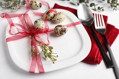 Festive Easter table setting with ribbon, floral decor and quail eggs on white background